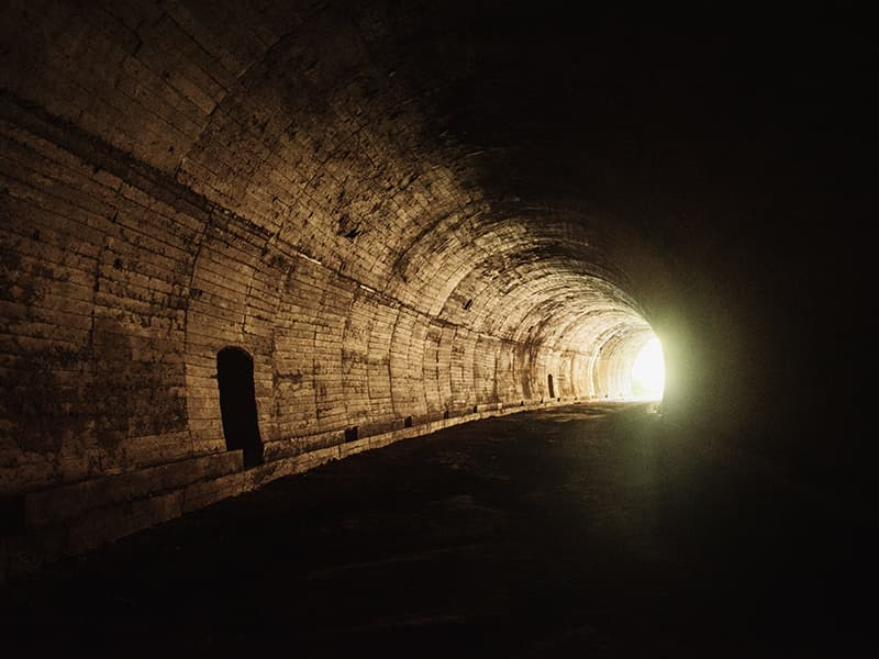 Dark tunnel with light at other end