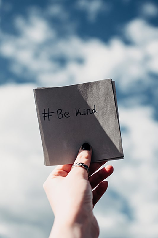 Hand holding a piece of paper with #Be Kind on it